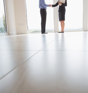 Estate agent and man shaking hands in new house