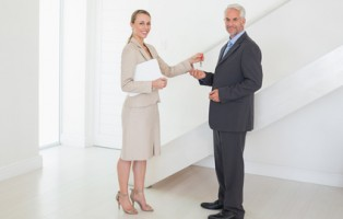 Smiling estate agent handing over keys to customer in empty house